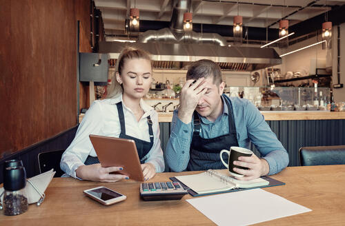 Depressed male and female entrepreneurs overwhelmed by finance problems