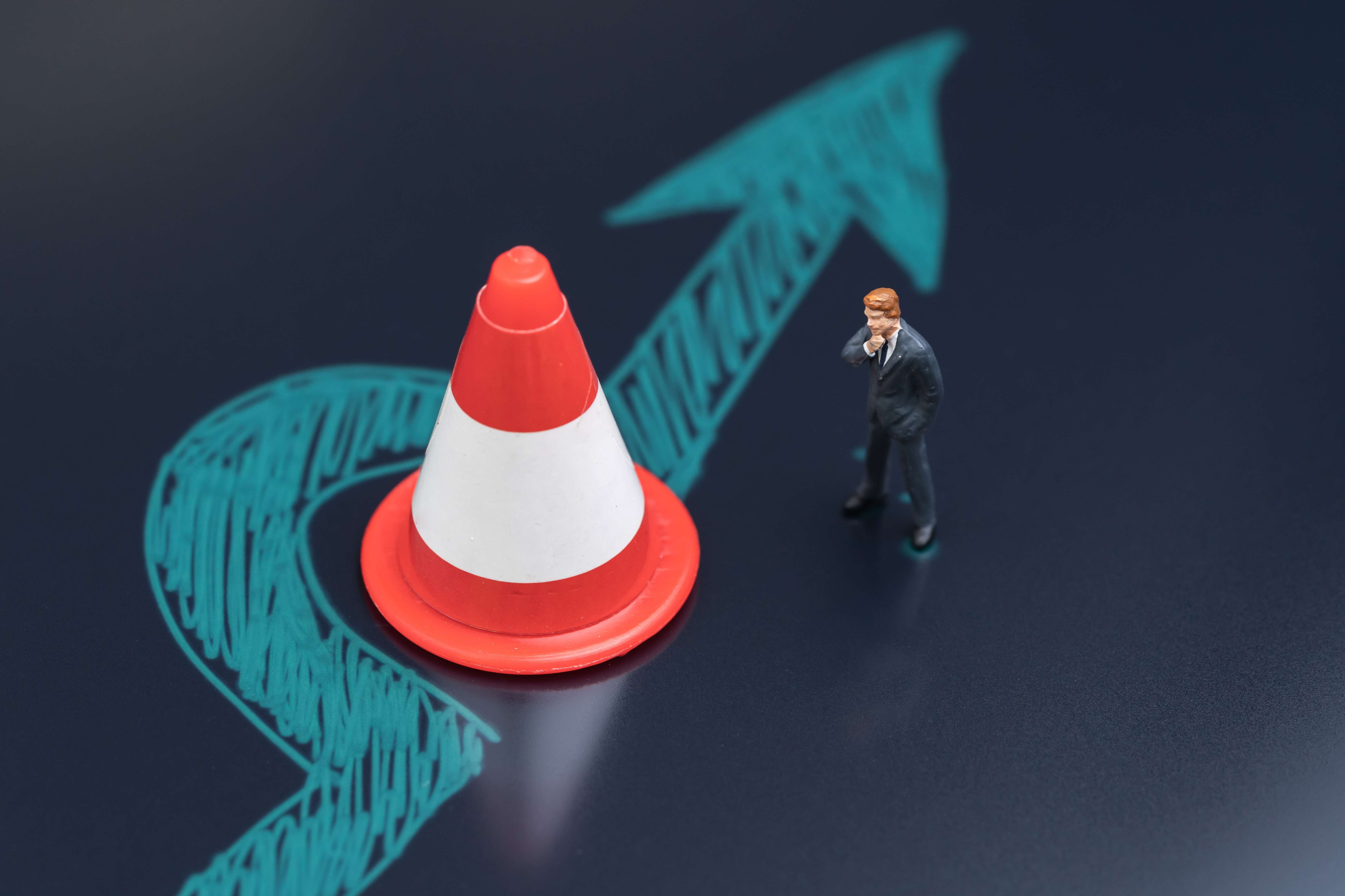 Obstacle, solution idea for business problem or blocker to success concept, miniature people businessman thinking with chalk drawing arrow turn pass the road block traffic pylon on dark blackboard