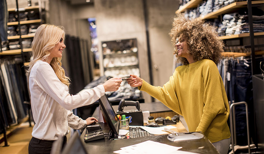 Attractive woman customer paying with credit card in fashion showroom