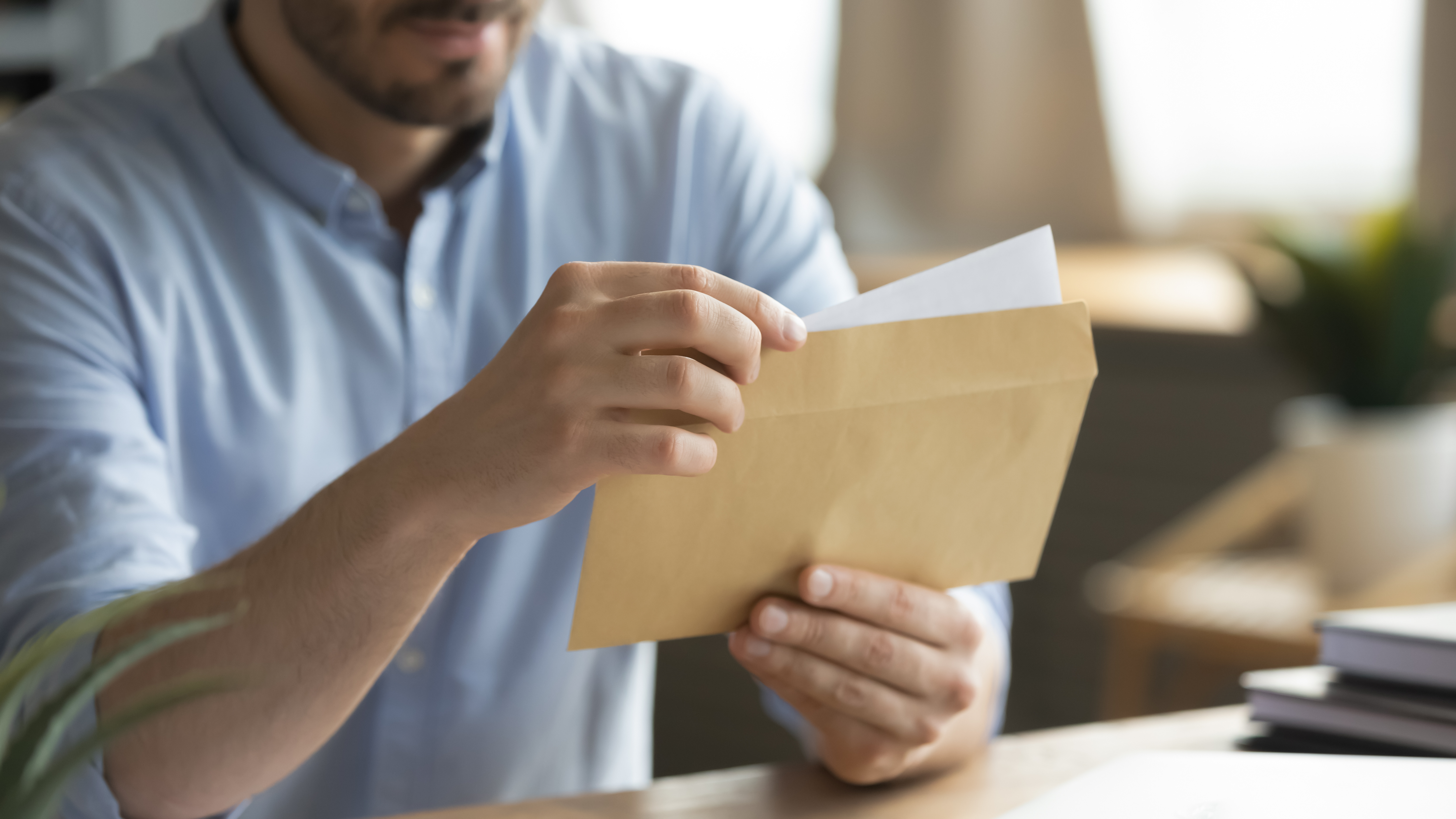 Close up young man opening envelope with paper correspondence. Curious businessman getting paper document by postal service or financial notification at workplace, received notification or invitation