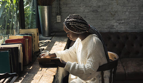 black woman with dreads writing in a journal