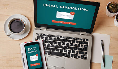 Email marketing logos on laptop and phone laid out on desk