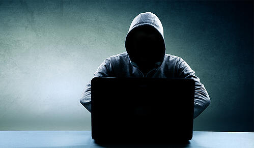 Hacker with hoodie on black laptop