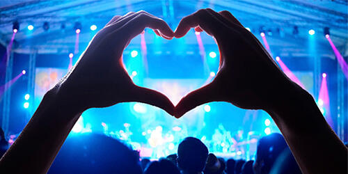 Hands throwing up a heart at concert
