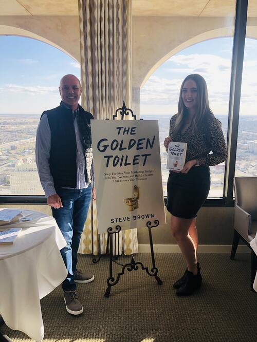 Steve Brown and Sarah Kreusel standing by The Golden Toilet Book cover poster