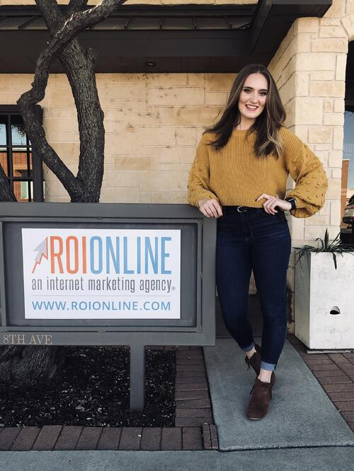 Sarah Kreusel next to ROI Online marketing agency sign outside of office