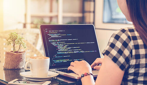 Programmer Typing New Lines of HTML Code. Laptop and Hand Closeup_