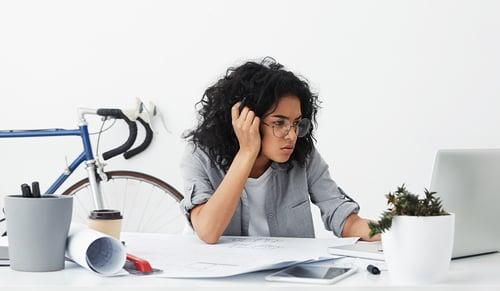 Shot of tired business enterpreneur dark-skinned female wearing big eyeglasses being worried while making her report_